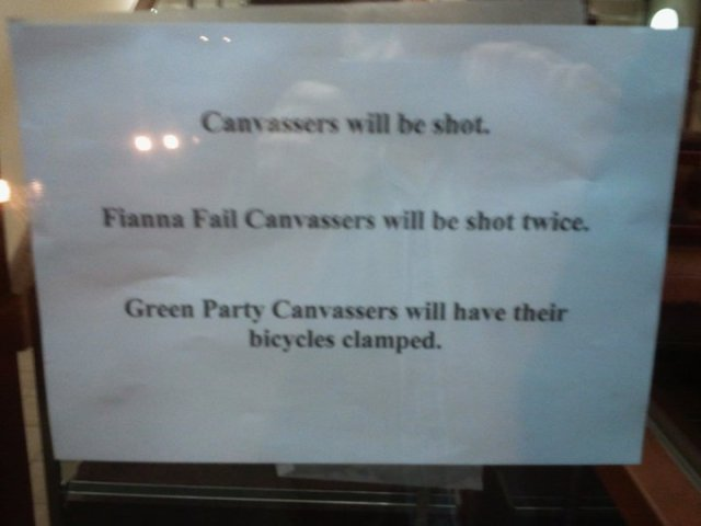 Poster on door: Canvassers will be shot. Fianna Fail Canvassers will be shot twice. Green Party Canvassers will have their bicycles clamped.